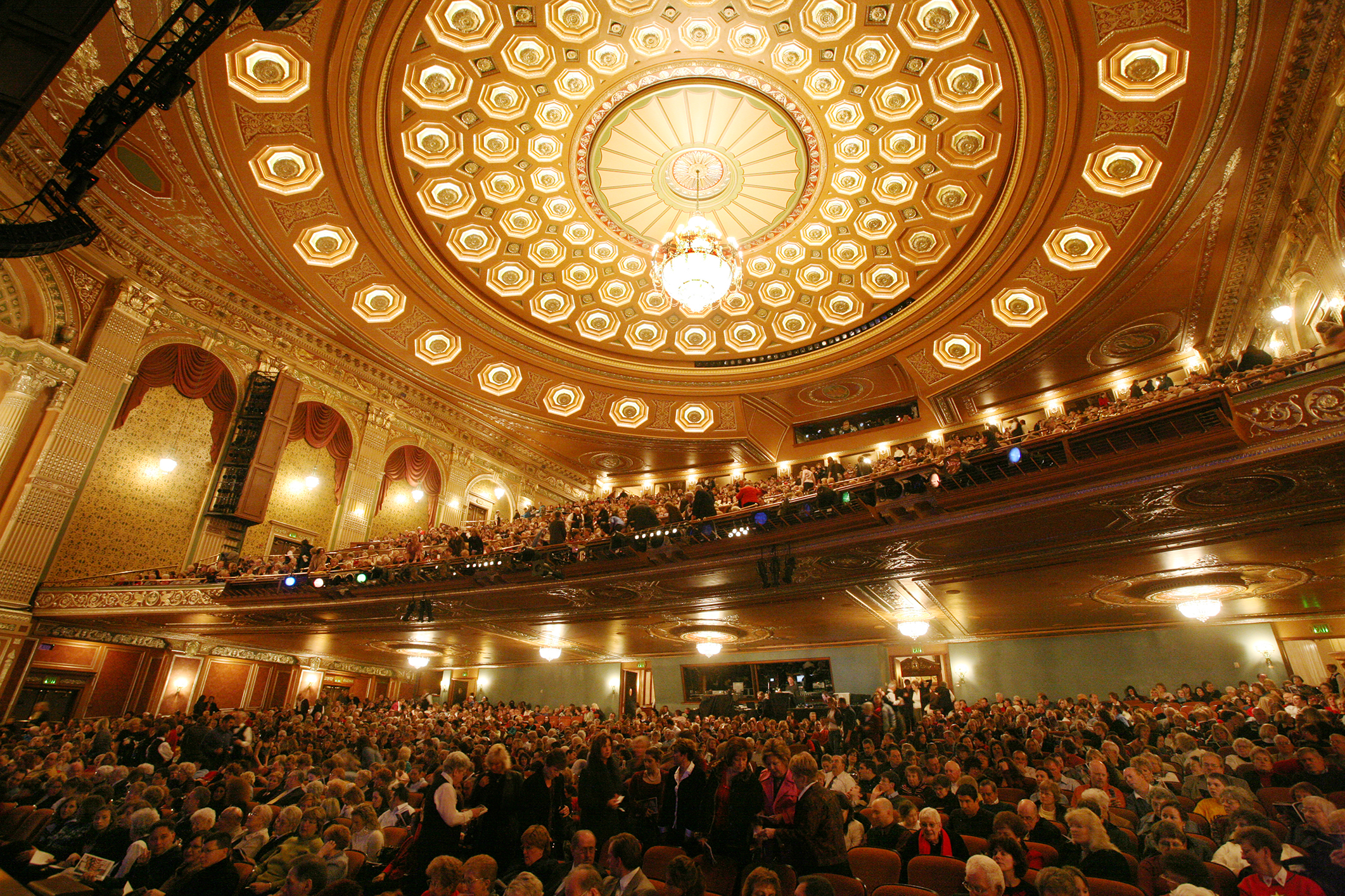 The ceiling of the Benedum Center concert hall, featuring ornate gold designs and a large, brightly-lit chandelier.